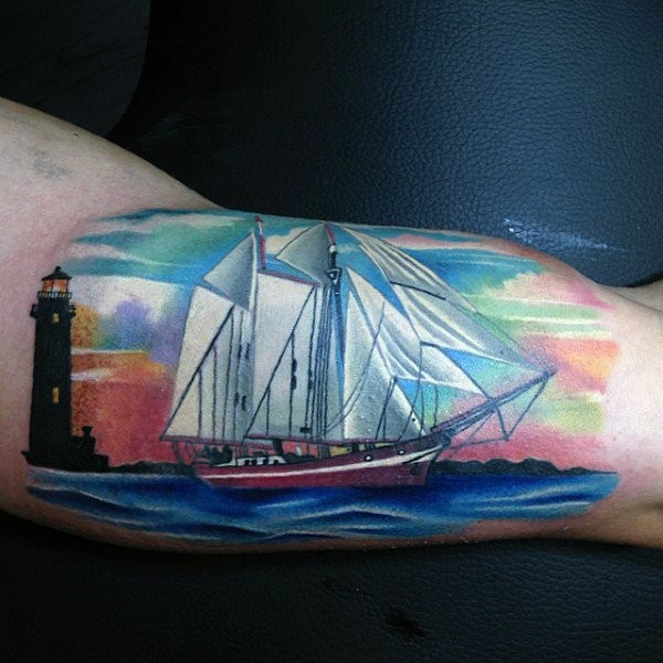 Usual colored biceps tattoo of modern sailing ship and lighthouse