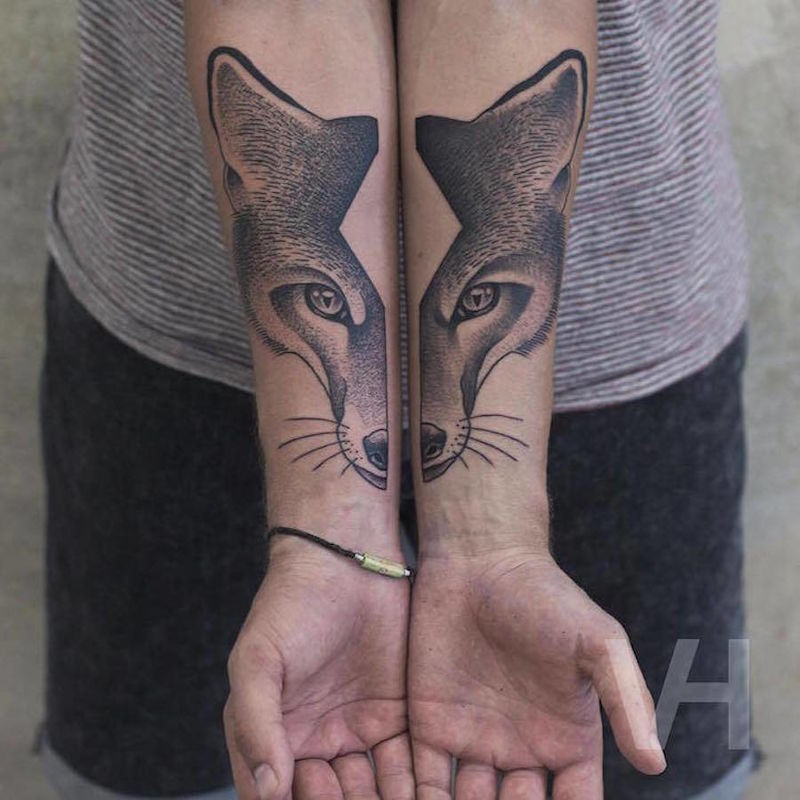 Usual designed divided fox head tattoo on forearm