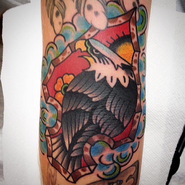 Usual old school style colored big ancient arrow head tattoo stylized with eagle tattoo on arm