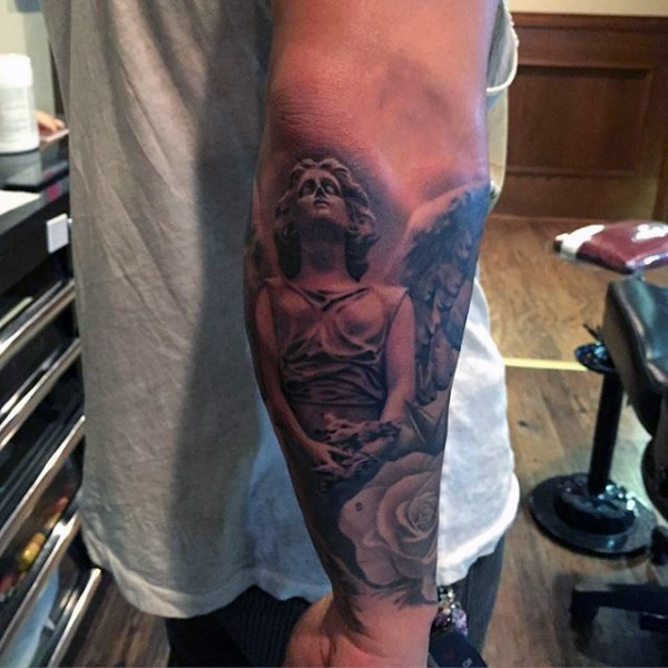 Usual painted black ink angel tattoo on forearm with rose