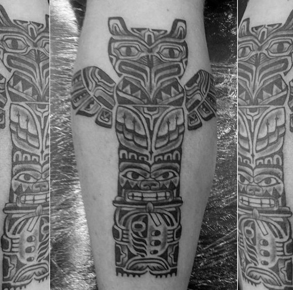 Usual style black and white tribal Gods statue tattoo on leg