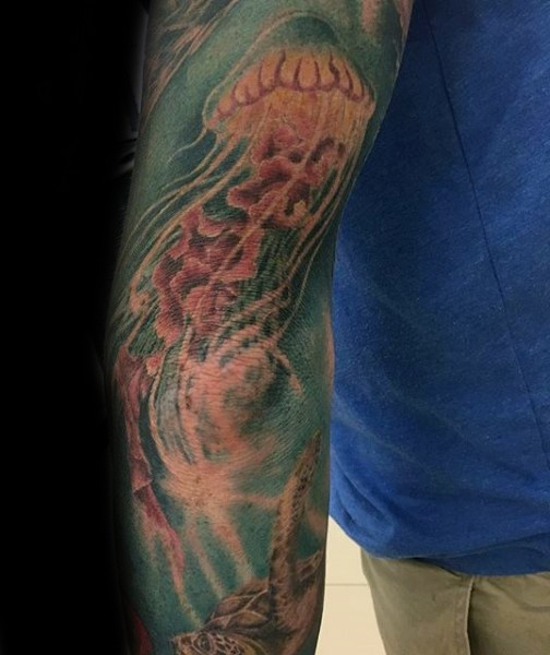 Usual style painted and colored big jellyfish with turtle tattoo on sleeve
