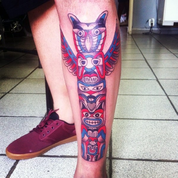Usual style painted and colored big tribal statue tattoo on leg