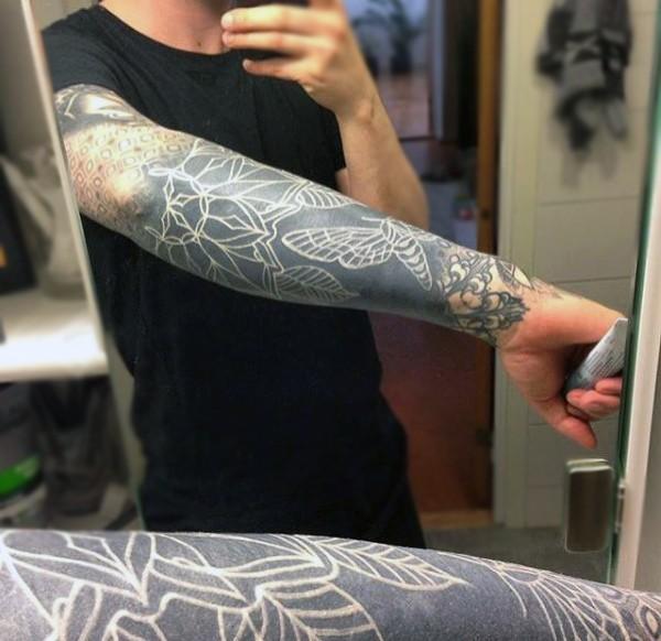 solito stile dipinto inchiostro bianco con fiori tatuaggio su braccio