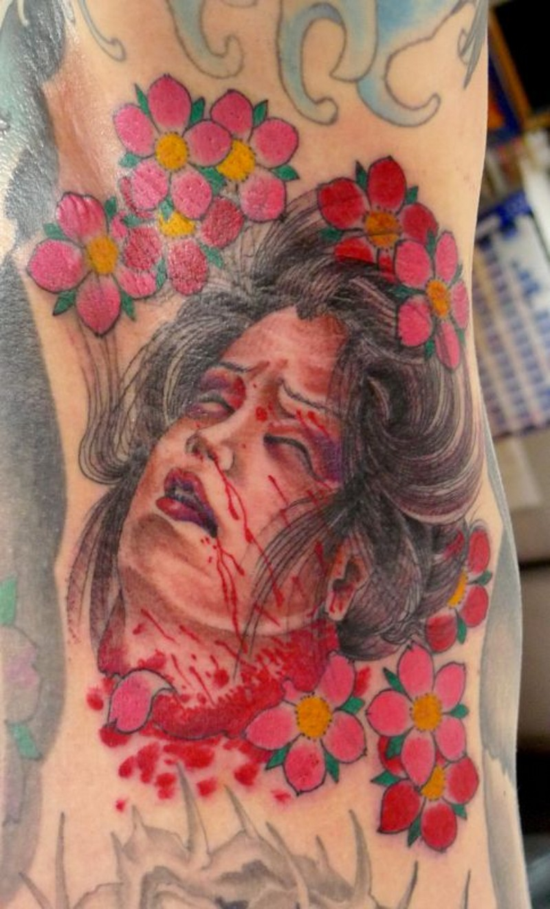 Usual terrifying colored severed head of Asian woman tattoo stylized with flowers