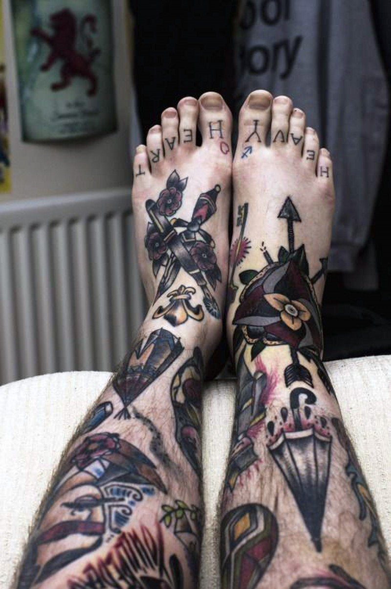 Various style multicolored tattoo on whole legs