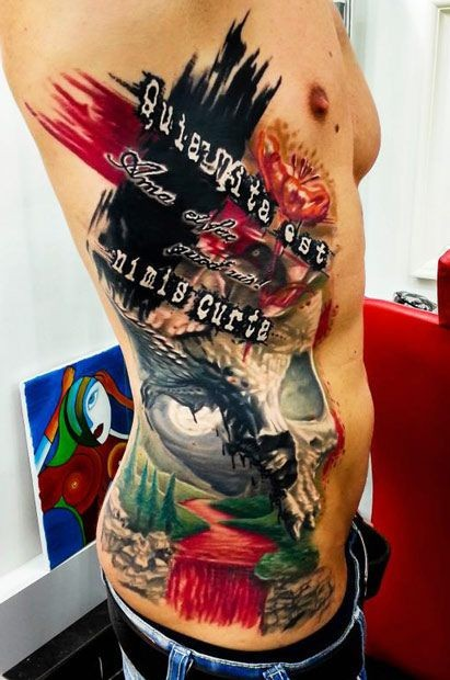 Various style painted big multicolored tattoo with skull and lettering on side