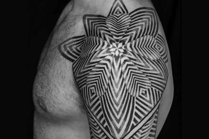 Very beautiful black and white tribal style flower tattoo on upper back zone