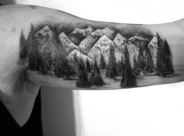 Very beautiful painted black ink mountain forest tattoo on arm