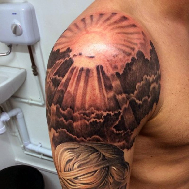 very beautiful painted colored sunrise shoulder tattoo with clouds