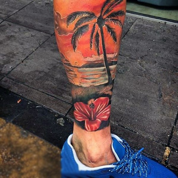 Very beautiful painted colorful beach sunset with palm tree and flower tattoo on leg