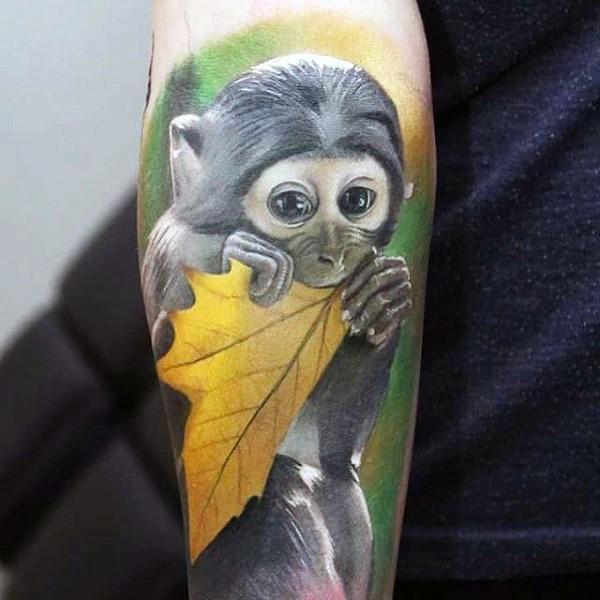 Very cute multicolored little monkey tattoo on arm