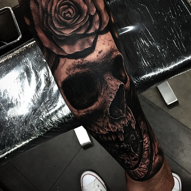 Very detailed black human skull tattoo on forearm with rose