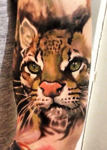 Very nice head of a wild cat tattoo on half sleeve