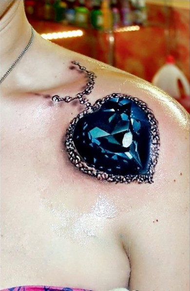 Very realistic 3D blue heart shaped diamond tattoo on shoulder