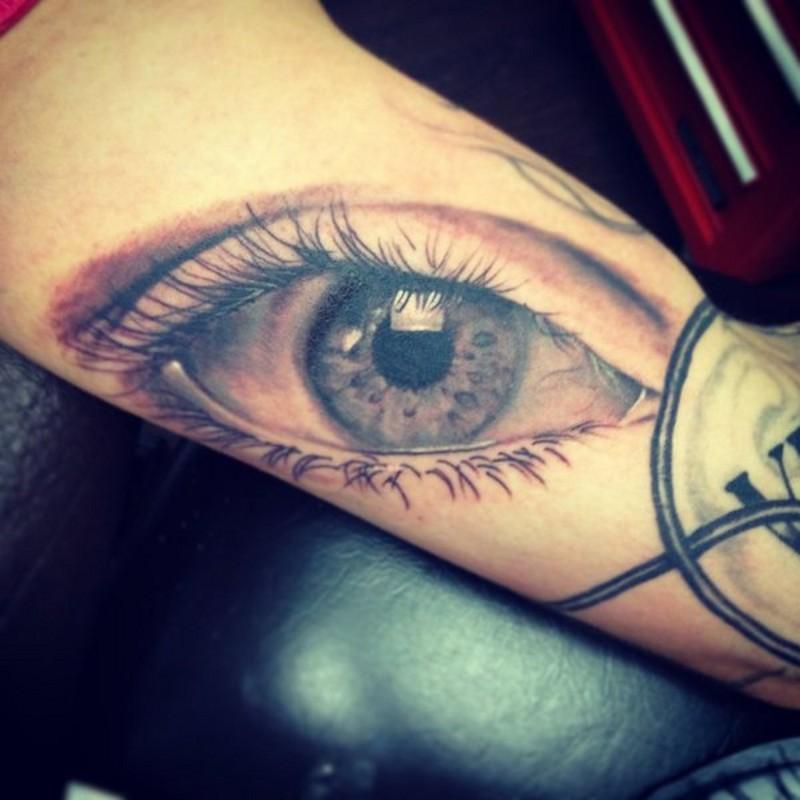 Very realistic colored big sad eye tattoo on arm