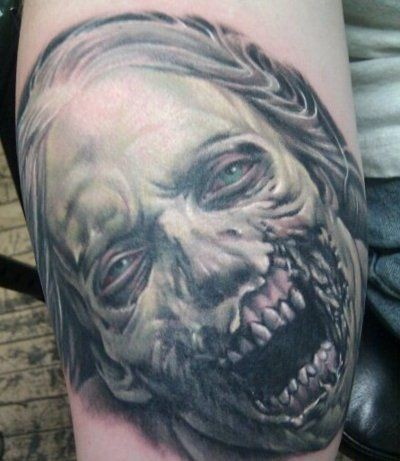 Very realistic designed and detailed colored evil zombie woman tattoo on arm