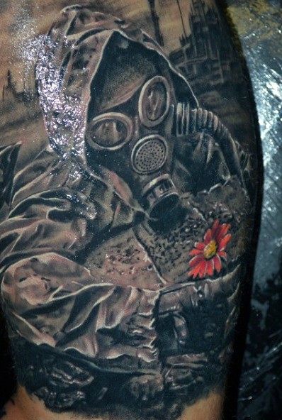Very realistic looking arm tattoo of stalker with gas mask and small flower
