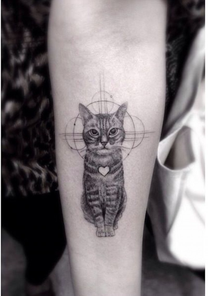 Very realistic looking black and white little cat with heart tattoo on arm