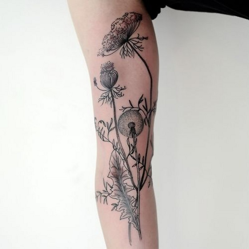 Very realistic looking black ink flowers tattoo on arm