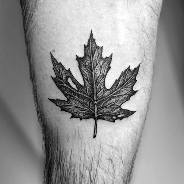 Very realistic looking black ink maple leaf tattoo on leg
