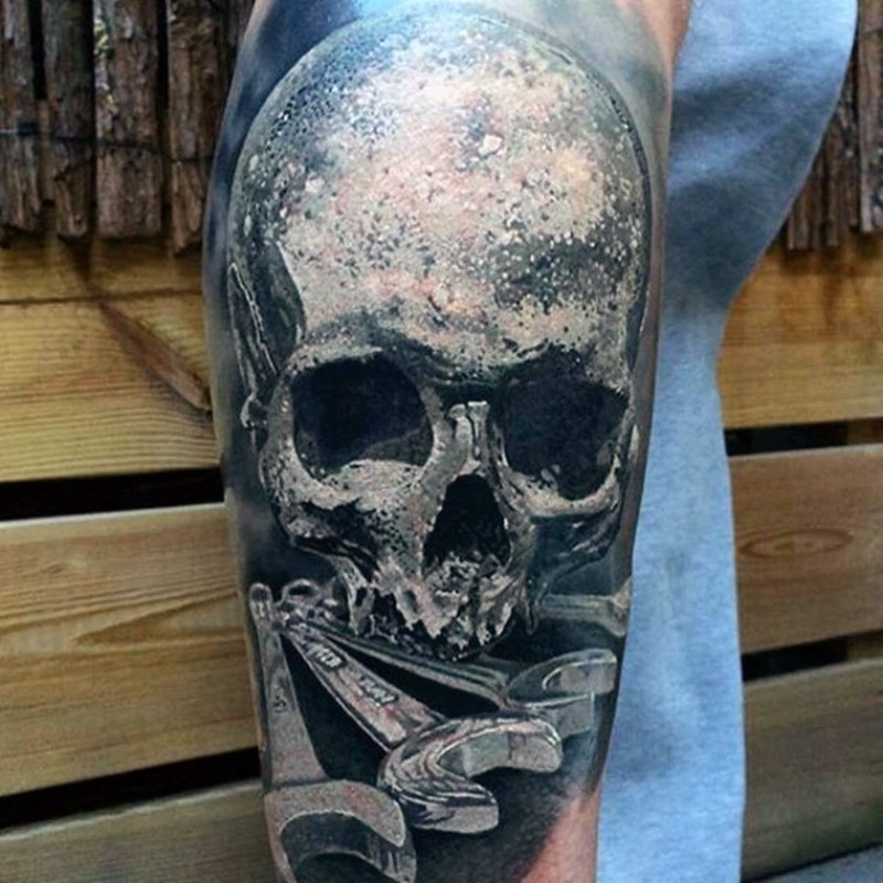 Very realistic looking detailed skull with spanners tattoo on arm