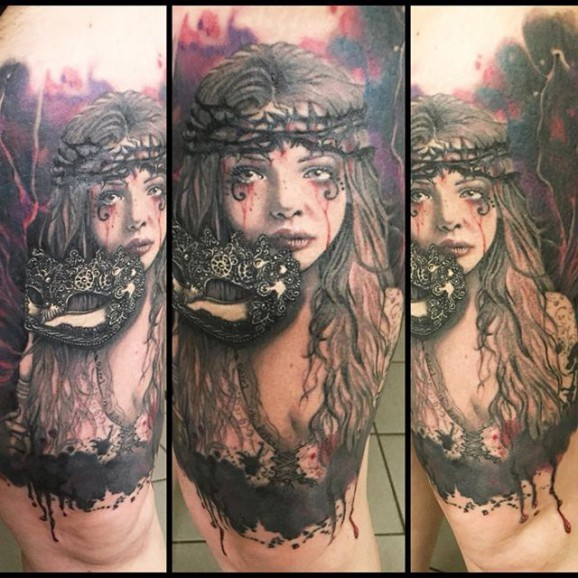 Very realistic looking horror style woman with mask tattoo on thigh