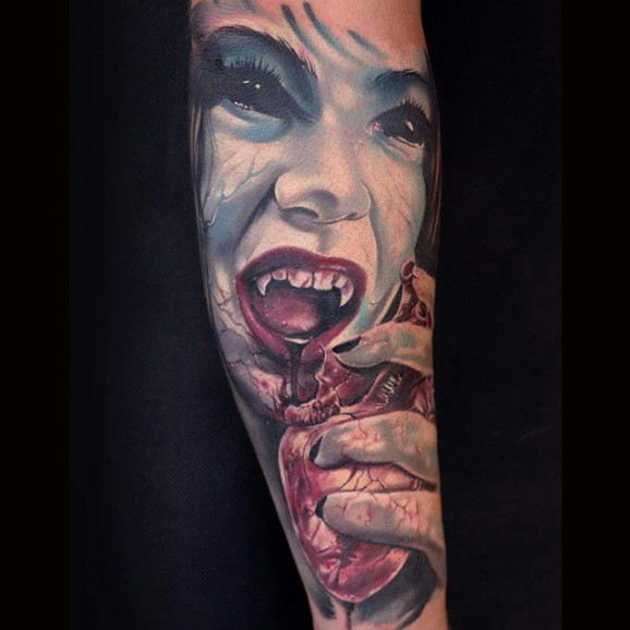 Very realistic looking multicolored woman zombie with bloody heart tattoo on sleeve