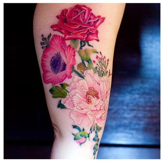 Very realistic multicolored various flowers tattoo on arm