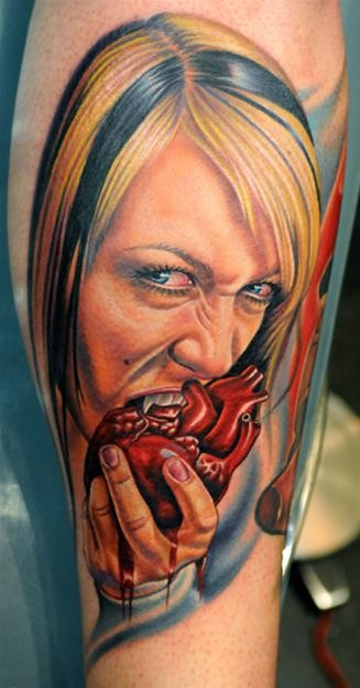 Very realistic painted and colored creepy bloody vampire woman eating humans heart tattoo on leg
