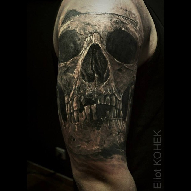Very realistic painted by Eliot Kohek upper arm tattoo of human skull