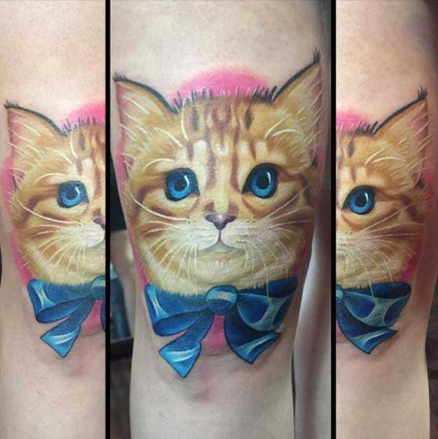 Very sweet colored thigh tattoo of cute painted kitten with blue bow