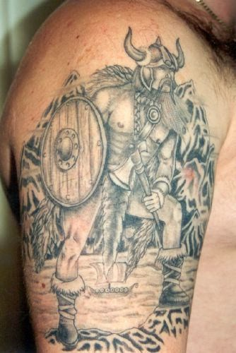 Viking in armor and with weapons tattoo