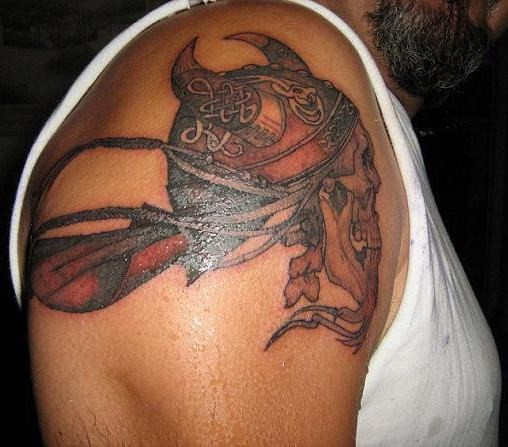Viking skull in a horned helmet tattoo on shoulder