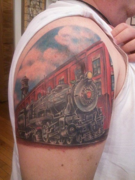 Vintage art style colored upper arm tattoo of steam train near old factory