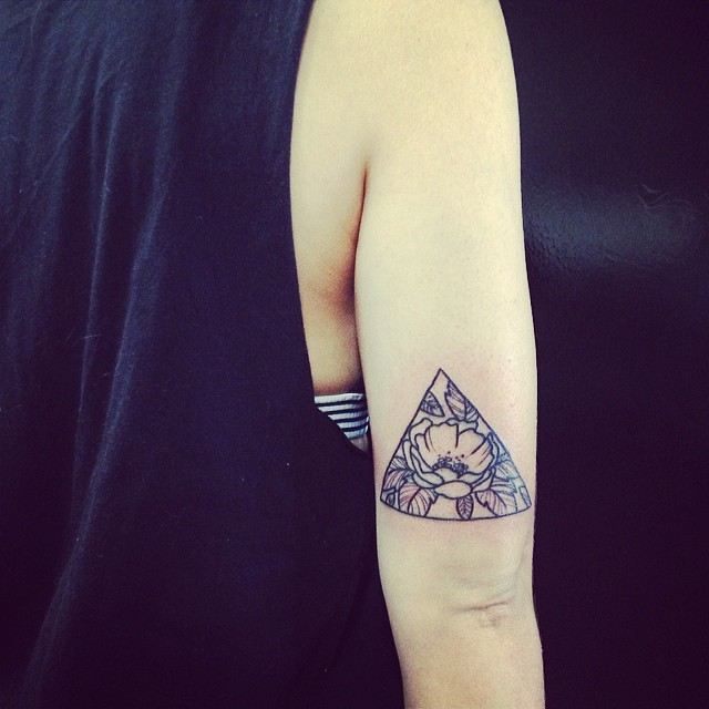 Vintage black ink arm tattoo of triangle stylized with wild flower