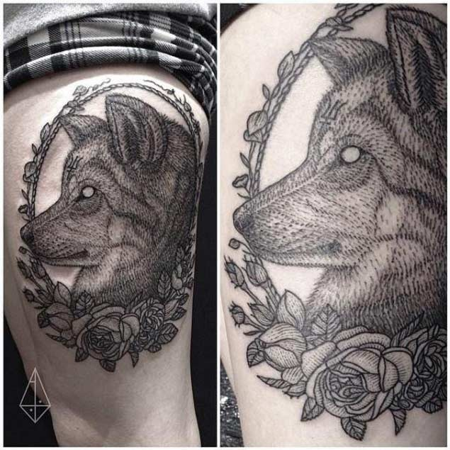Vintage black ink demonic wolf portrait tattoo on thigh stylized with flowers