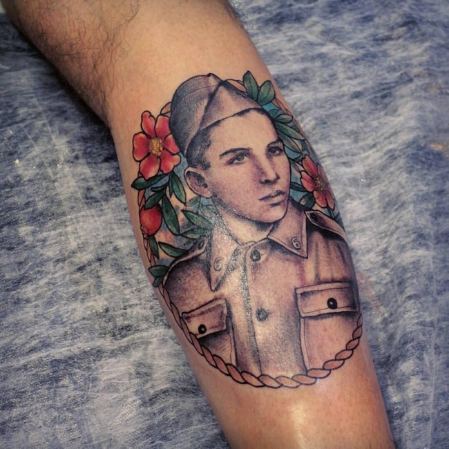 Vintage colored leg tattoo of soldier man portrait with flowers