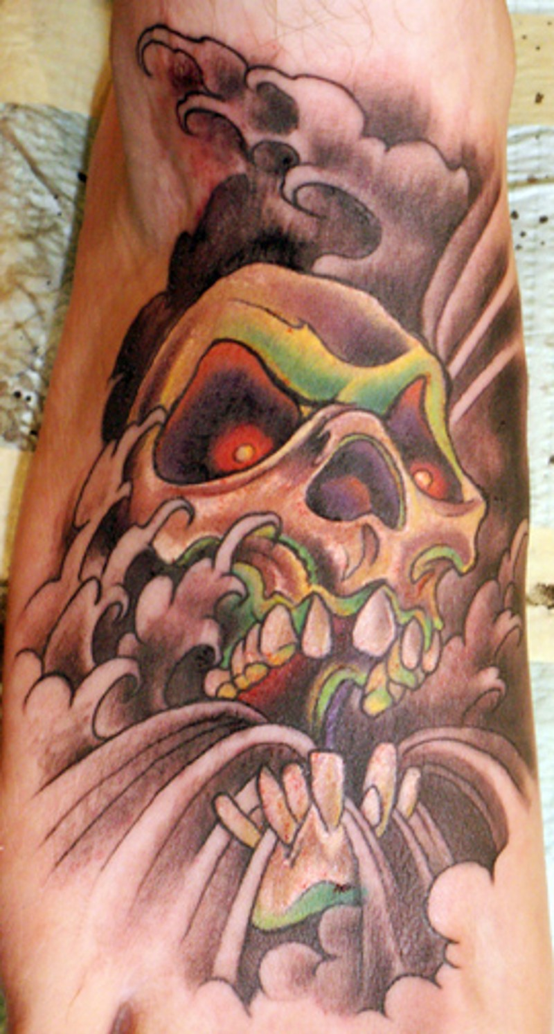 Vintage comic books style colored demonic skull tattoo on forearm with clouds