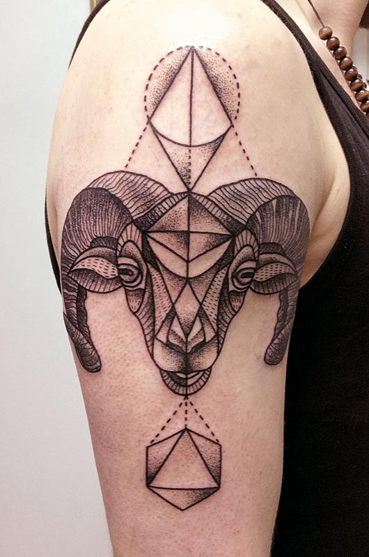 Vintage like black ink big goat head tattoo on shoulder stylized with geometric figures
