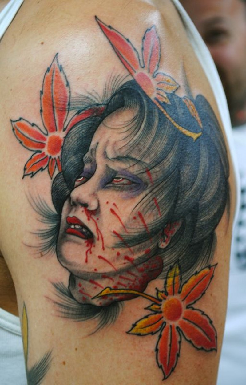 Vintage like creepy colored Asian woman severed head bloody head tattoo on shoulder with leaves