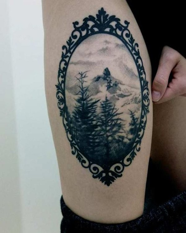 Vintage portrait like black ink thigh tattoo of mountain forest