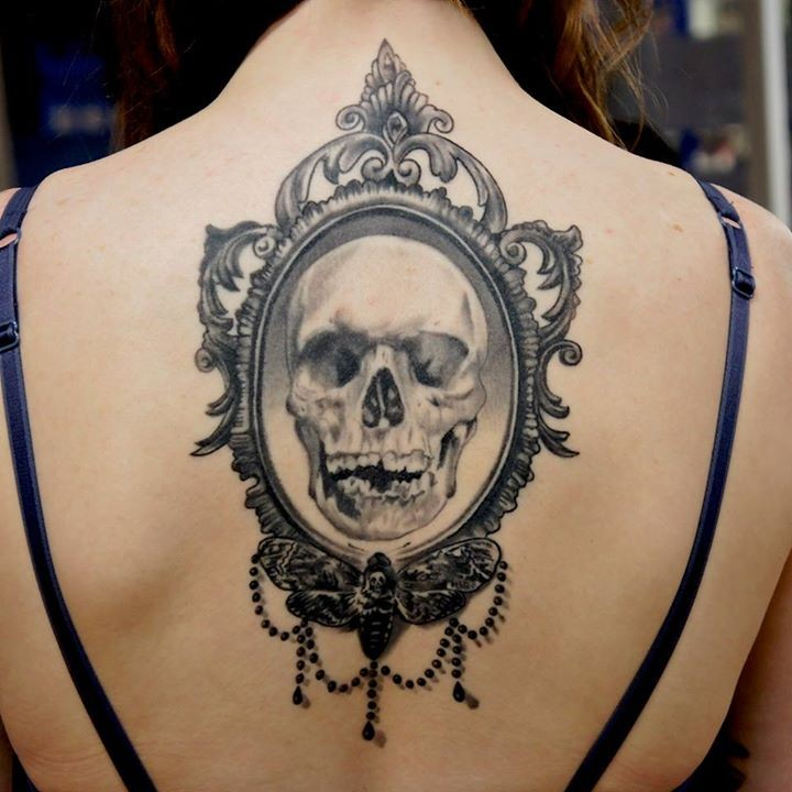 Vintage style black and white human skull portrait tattoo on back stylized with night butterfly
