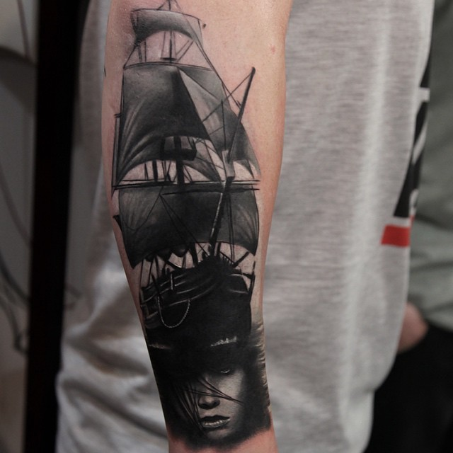 Vintage style black and white sailing ship tattoo on forearm with mystic woman portrait