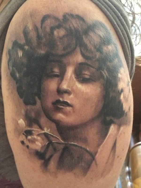 Vintage style black and white shoulder tattoo of woman portrait with flower