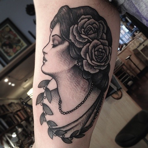 Vintage style black ink biceps tattoo of woman with flowers