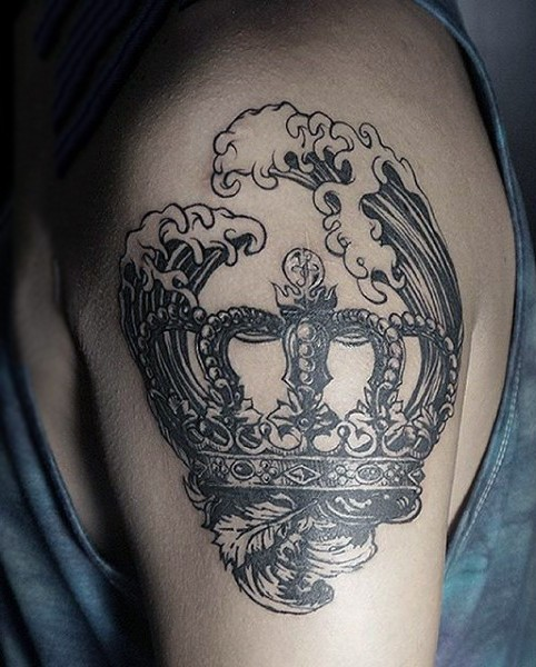 Vintage style black ink crown tattoo on shoulder with waves
