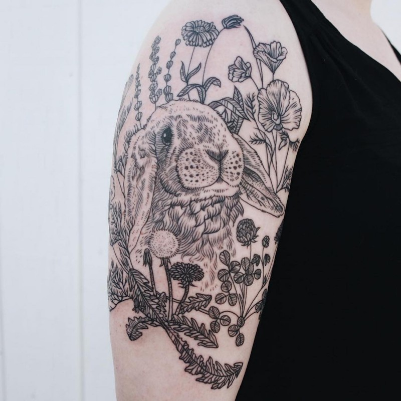 Vintage style black ink cute rabbit tattoo on shoulder with various wildflowers