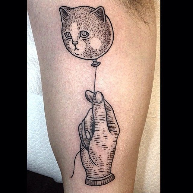 Vintage style black ink hand with cat shaped balloon on biceps