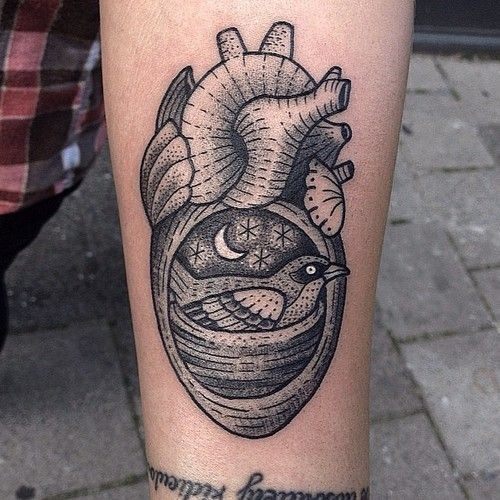 Vintage style black ink heart shaped forearm tattoo stylized with bird in nest